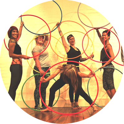 Hula Hoopers posing with their hoops in a Hoop Sparx hula hoop class