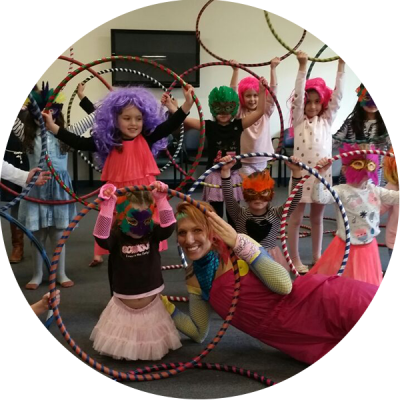 Donna Sparx with kids and hula hoops at hula hoop kids party. Kids are wearing wigs and masks.