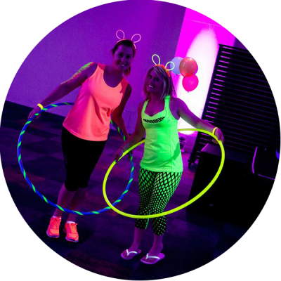 Two hula hoopers posing with their UV active hoops during a Hoop Sparx workshop