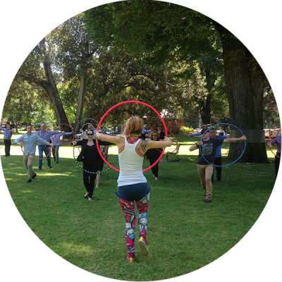 Donna Sparx teaching hula hoops to a group of people as part of a corporate team building activity